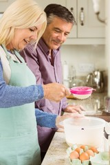 Happy blonde preparing dough with husband