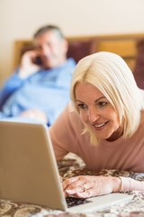 Happy mature blonde using laptop on bed
