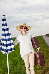 Woman wearing sun screen and holiday suitcase