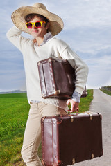 Woman with straw hat and sunglasses wearing holiday suitcase