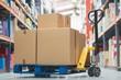 Leinwanddruck Bild - Boxes on trolley in warehouse
