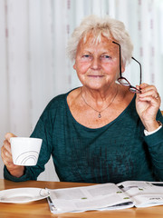 Elderly woman with cup looks up from reading