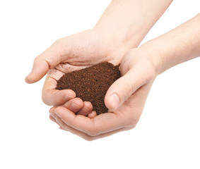 Two hands holding a handful of ground soil
