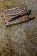 Beautiful ornamented old diary and pen