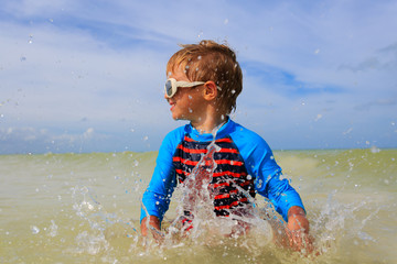 little boy playing with water on tropical beach
