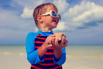 little boy holding seashells on summer beach