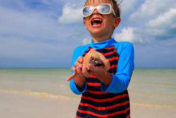 little boy holding seashells on summer beach