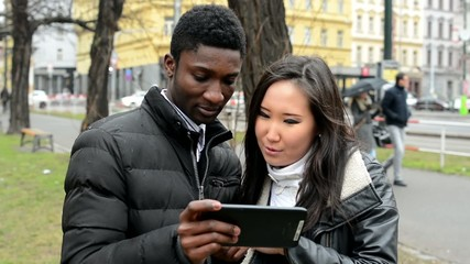 Happy couple work on tablet - black man and asian woman - street