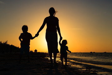 mother and two kids walking on at sunset