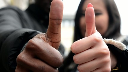 Happy couple show thumb on agreement - black man and asian woman