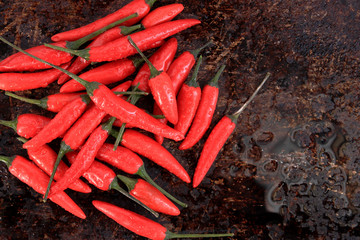 Bunch of red thai chili peppers on brown background