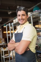Smiling worker in apron with arms crossed