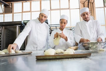 Concentrated colleagues kneading uncooked dough