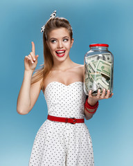 Cheerful attractive young lady holding jar of money