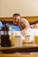 Happy mature couple having breakfast in bed