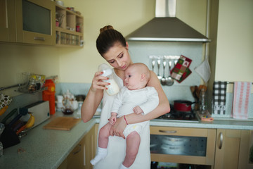 young mother prepares meal for baby