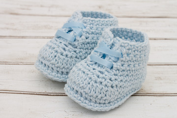 Pale Blue Baby Booties on wood background