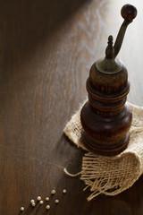 Alte Pfeffermühle und getrocknete Pfefferkörner