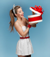 woman holding an open gift box and looking at the present