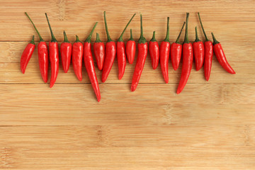 Row of red thai chili peppers on wood background