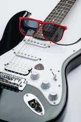 Electric guitar with red sunglasses and mediator