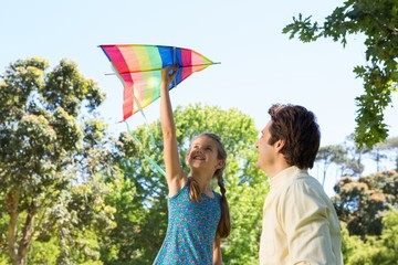 Father and daughter playing with kite