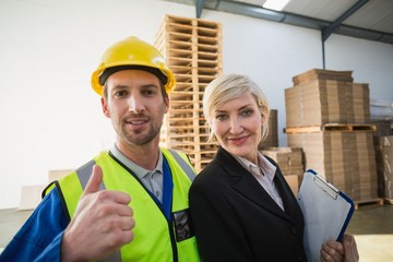 Portrait of smiling warehouse worker and his manager