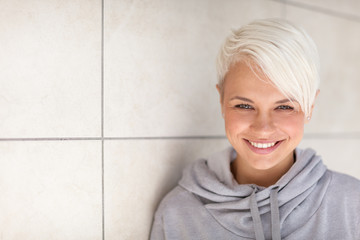 Casual portrait of blonde woman standing next to a wall