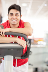 Smiling man at the gym standing next to the bicycle