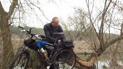 Adult  man  cyclist eats outdoors near river