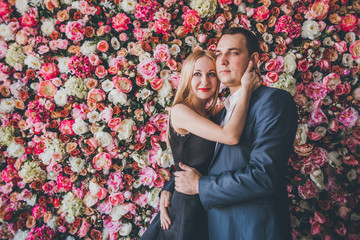 Loving couple in the studio flowers wall