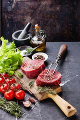 Raw fresh marbled meat Steak, seasoning and meat fork on dark ma