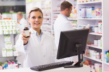 Pharmacist showing medicine bottle