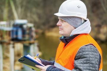 Engineer with documentation near power transformer