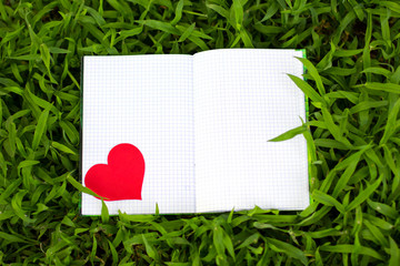 Blank notepad for copy space on green grass. Love to write