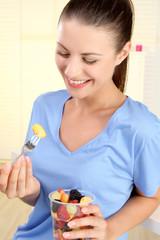 Junge Frau isst einen Obstsalat