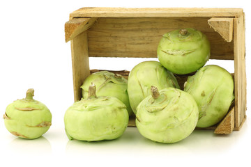 freshly harvested kohlrabi in a wooden crate on a white backgrou