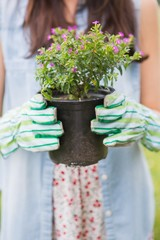 Happy woman holding potted flowers