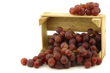 fresh red seedless grapes on the vine in a wooden crate