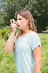 Pretty blonde using an asthma inhaler