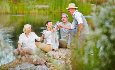 Gruppe Senioren prostet sich mit Sekt zu