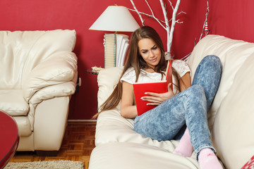 Young woman student learns at home on the sofa