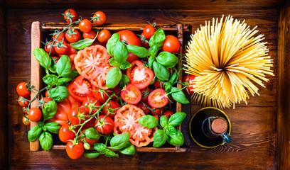 Italian food.Spaghetti, tomatoes, basil on rustic background.