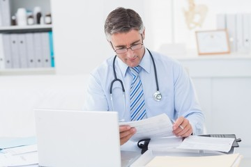 Doctor reading document at table