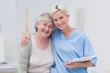 Friendly nurse with arm around senior patient in clinic