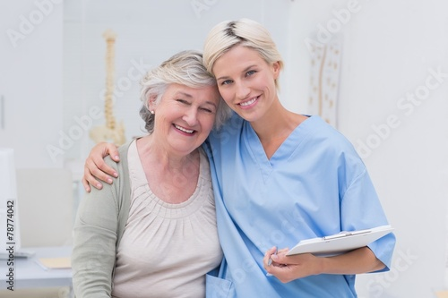 Friendly nurse with arm around senior patient in clinic - 78774042