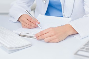 Female doctor writing prescriptions at table