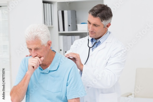 Doctor examining coughing senior patient - 78775074