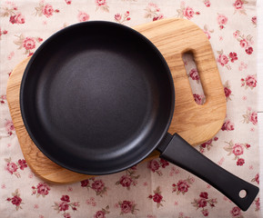 Empty frying pan on wooden background.