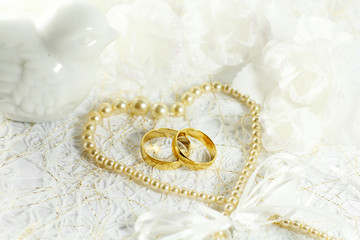 Two golden wedding rings with seamless flower decorations